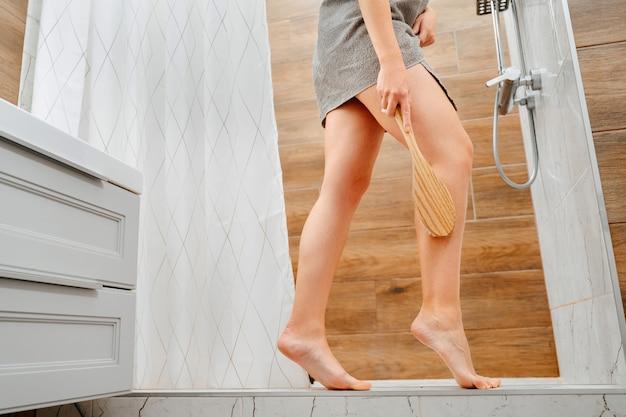 La peau lisse et tendue des jambes sur fond de salle de bain moderne est massée et lavée