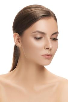 La peau parfaite et propre du visage de la femme sur un mur blanc