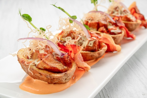 Peau de pomme de terre avec bacon et fromage et sauce tomate sur une table en bois