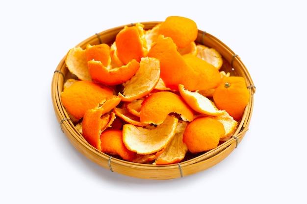 Peaux d'orange dans un panier en bambou sur une surface blanche