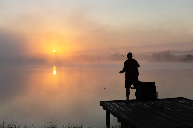 Pêche à l'aube pêcheur sur fond de ciel matinal