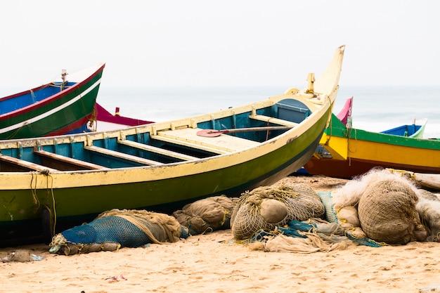 Pêche de bateaux colorés et filets sur la plage.