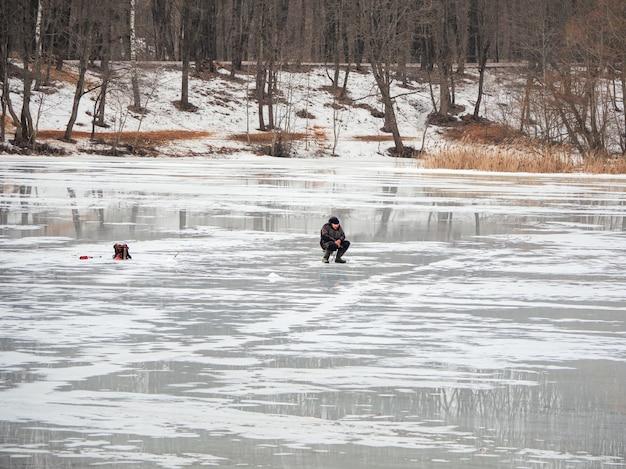 Pêche dangereuse sur la glace printanière mouillée. pêcheur sur glace fondante humide. russie.