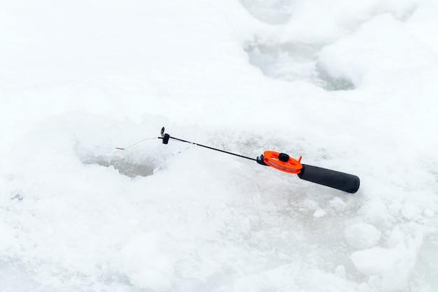 Pêche d'hiver sur glace. appât secoué dans un trou de glace.