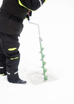 Pêche hivernale sur glace. homme perçant un trou dans la glace. détente à l'état sauvage