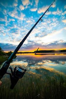 Pêche sur le lac au coucher du soleil d'été