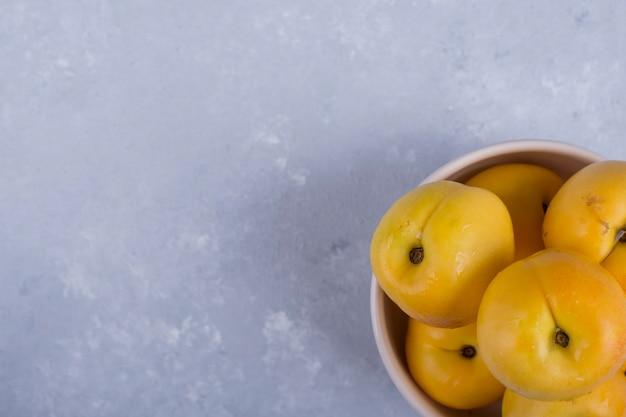 Pêches jaunes dans un bol en céramique blanche dans le coin inférieur