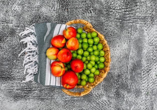 Pêches et légumes verts dans un panier en osier et un tissu de pique-nique sur gris grunge. vue de dessus.