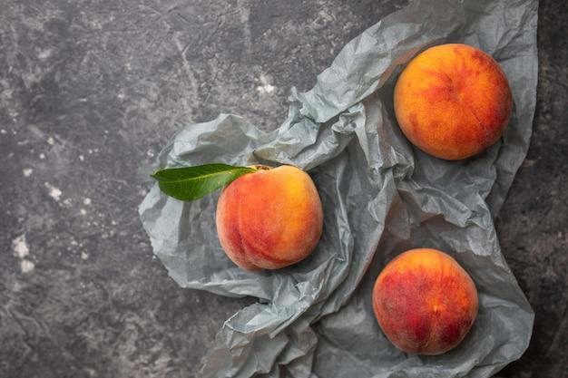 Pêches ou nectarines dans une assiette en pierre grise foncée avec feuilles, vue de dessus