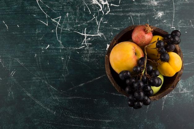 Pêches et raisins dans un bol en bois sur tableau noir