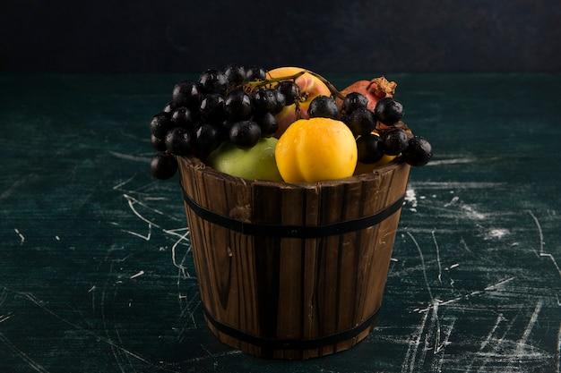 Pêches et raisins dans un seau en bois sur tableau noir