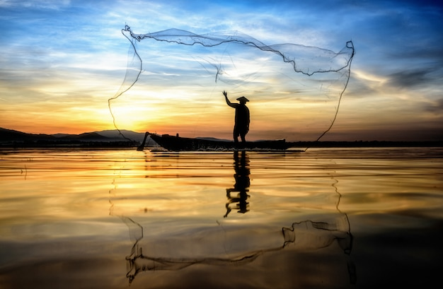 Pêcheur en action lors de la pêche dans le lac, thaïlande
