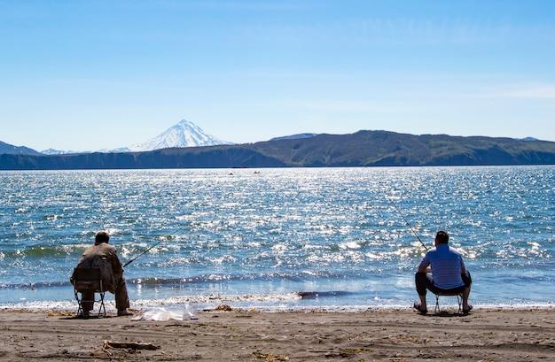 Pêcheur assis et pêchant sur la plage de l'océan pacifique