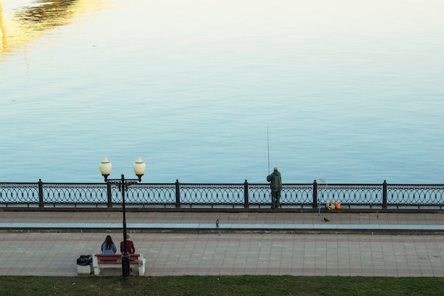 Un pêcheur attrape du poisson sur la rive de la rivière de la ville au début du printemps