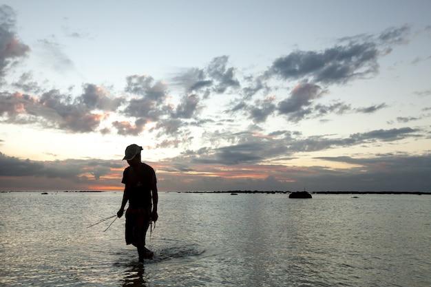 Un pêcheur attrape un poisson dans l'océan au coucher du soleil.