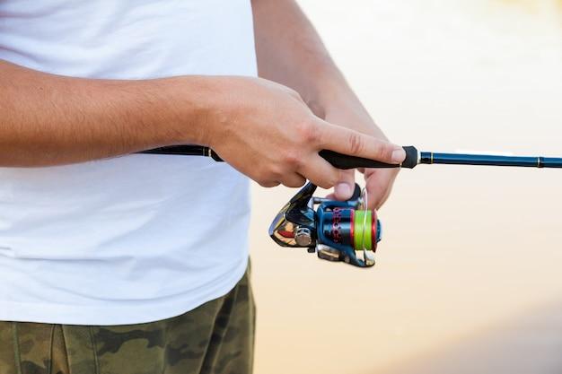 Pêcheur attrape un poisson. mains d'un pêcheur avec une canne à pêche en main agrandi.