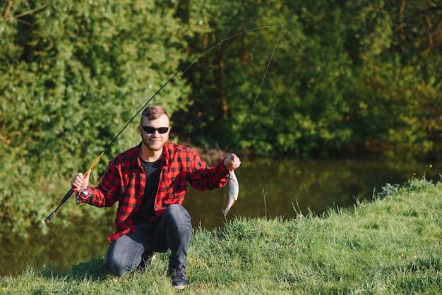 Pêcheur au bord de la rivière avec une prise de poisson