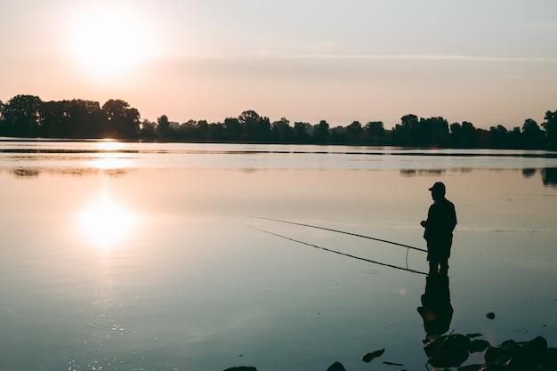 Pêcheur à l'aube de la pêche sur une canne à pêche