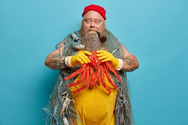 Pêcheur barbu habile tient la grosse pieuvre dans les mains prises avec un filet de pêche, pose au port, porte des gants en caoutchouc jaune