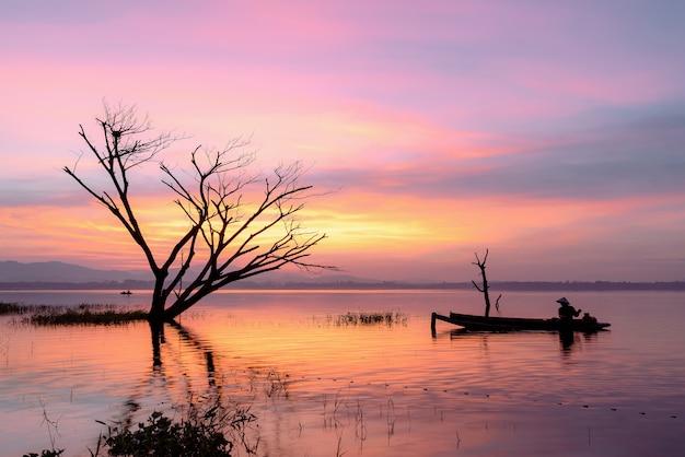 Pêcheur sur un bateau en bois jetant un filet pour attraper des poissons d'eau douce dans un réservoir au lever du soleil.