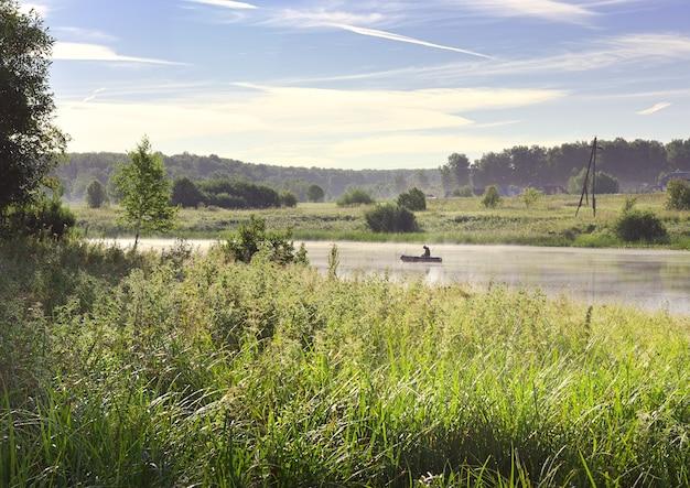 Pêcheur sur un bateau sur le lac un canot pneumatique à la surface de l'eau parmi les roseaux