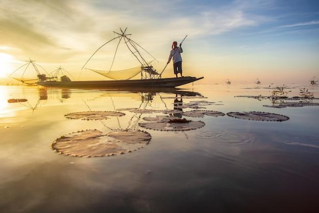 Pêcheur sur le bateau à longue queue le matin et épuisette carrée géante au village de pakpra