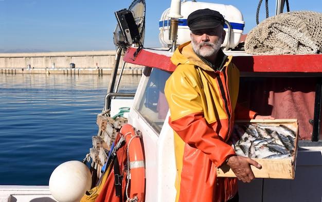 Pêcheur avec une boîte de poisson à l'intérieur d'un bateau de pêche
