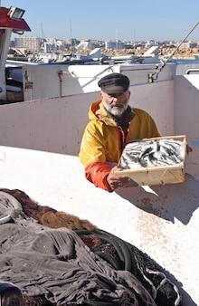 Pêcheur avec une boîte à poisson à l'intérieur d'un bateau de pêche