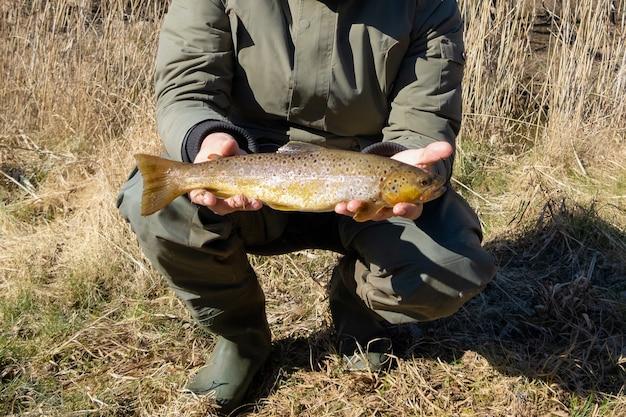 Pêcheur avec des bottes en caoutchouc pêche à la truite dans un ruisseau sur une journée ensoleillée