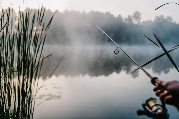 Pêcheur avec canne, moulinet à tambour sur la rive du fleuve. brouillard sur fond de lac.
