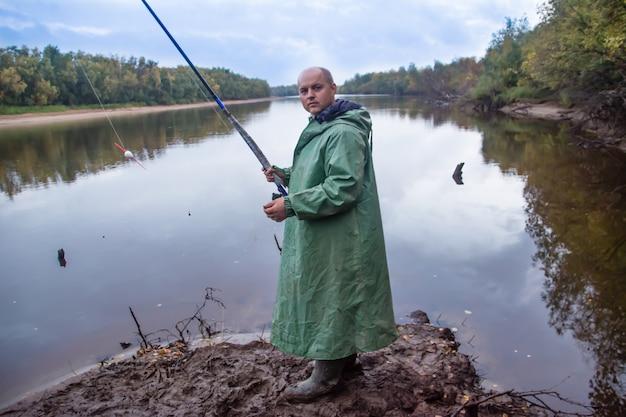 Le pêcheur avec canne à pêche debout dans la boue. faire de la pêche. le canal de la rivière nadym.yamal.