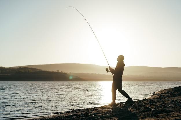 Pêcheur avec canne à pêche sur le lac
