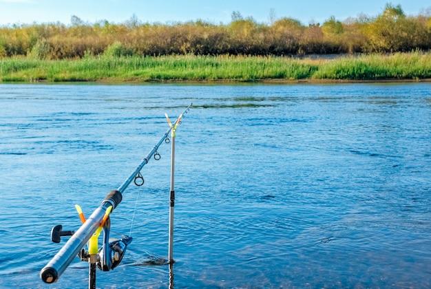 Pêcheur de canne à pêche sur des supports sur un fond d'eau