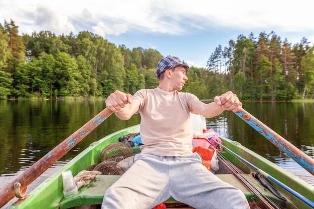 Pêcheur avec des cannes à pêche pêche dans un bateau en caoutchouc sur un lac ou une rivière