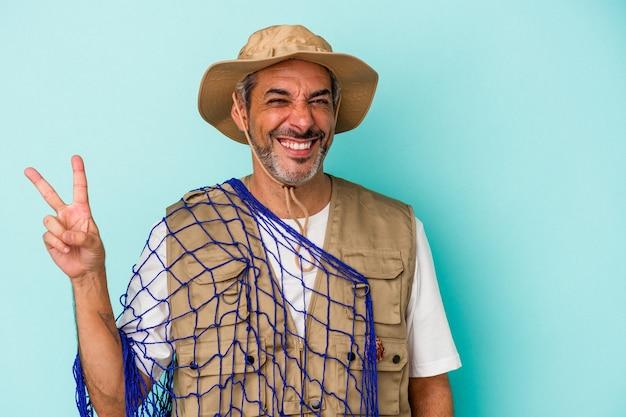 Pêcheur caucasien d'âge moyen tenant un filet isolé sur fond bleu joyeux et insouciant montrant un symbole de paix avec les doigts.