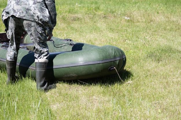 Pêcheur ou chasseur en tenue de camouflage et de hautes bottes en caoutchouc plie un bateau gonflable sur l'herbe