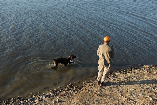 Pêcheur debout au bord de la rivière et essayant d'attraper un poisson. sport, loisirs, mode de vie.