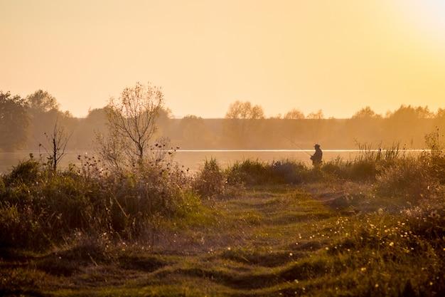 Pêcheur avec un équipement de pêche sur la rive du fleuve