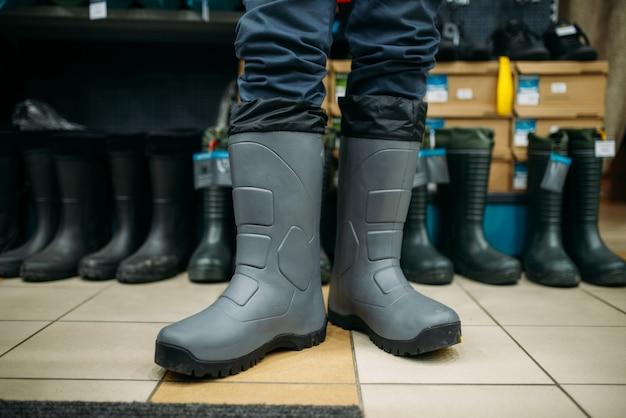 Pêcheur essaie des bottes en caoutchouc dans un magasin de pêche