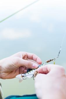 Pêcheur fixant le leurre au sabot de la canne à pêche
