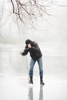 Un pêcheur de glace perce un trou avec une tarière électrique sur un lac gelé