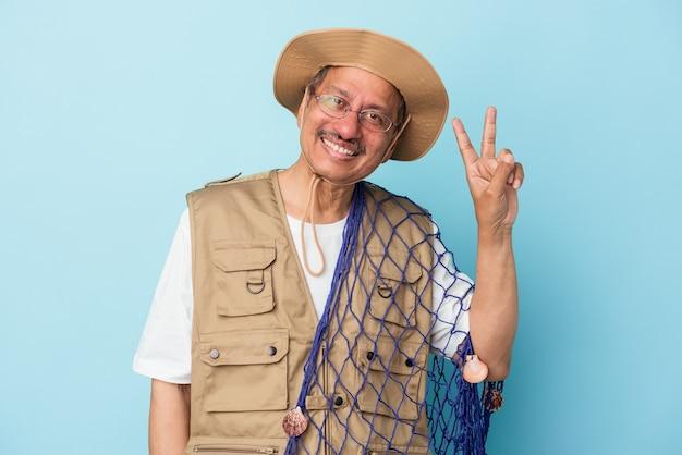 Pêcheur indien senior tenant un filet isolé sur fond bleu joyeux et insouciant montrant un symbole de paix avec les doigts.