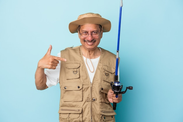 Pêcheur indien senior tenant une tige isolée sur fond bleu personne pointant à la main vers un espace de copie de chemise, fier et confiant