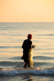 Le pêcheur a jeté un filet la mer le matin, au lever du soleil