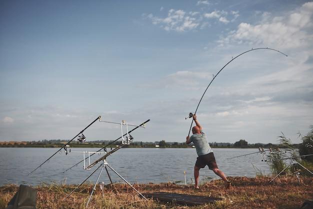 Le pêcheur lance un appât avec appât. aujourd'hui, il attrapera un gros poisson. chasse et sport de loisir