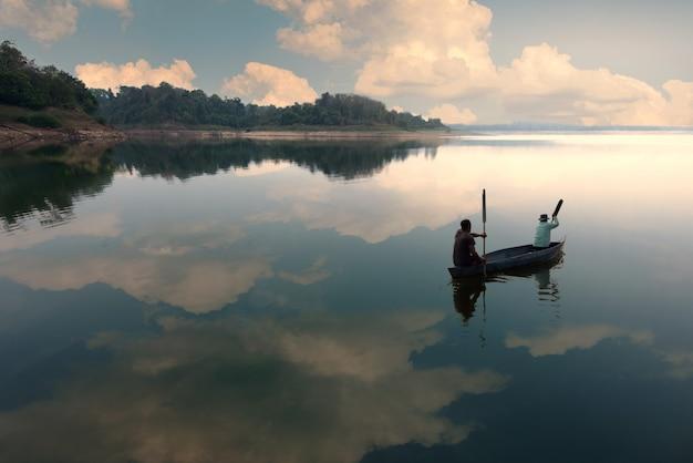 Un pêcheur à la ligne pêchant sur le lac avec un ciel bleu - image