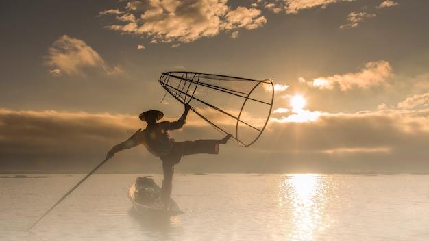 Un pêcheur local utilise un filet de pêche dans le lac taungthaman