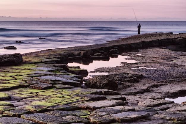 Pêcheur en mer avec canne.