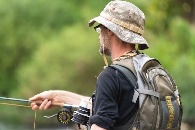 Pêcheur pêchant sur la rivière, tenant une canne à pêche.