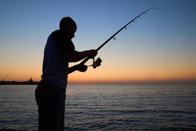 Pêcheur pêche sur le lac. silhouette au coucher du soleil